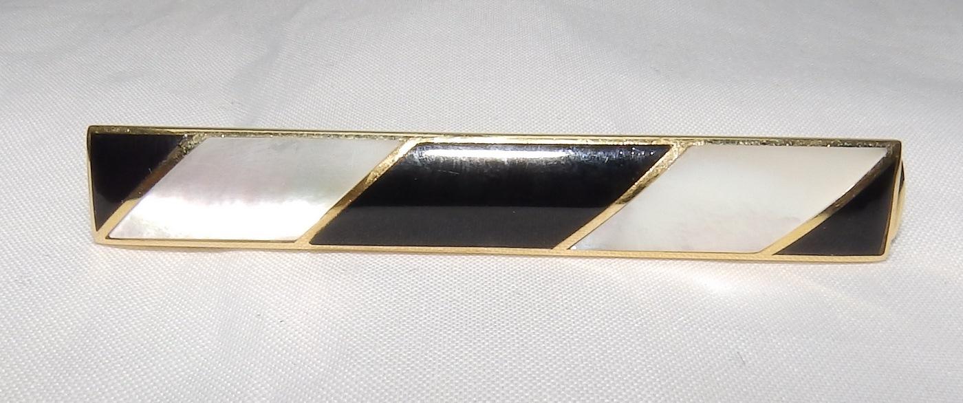 Pisacorbata en Oro de 18k con incrustaciones de nácar y esmalte negro. Peso: 11,10 gr.