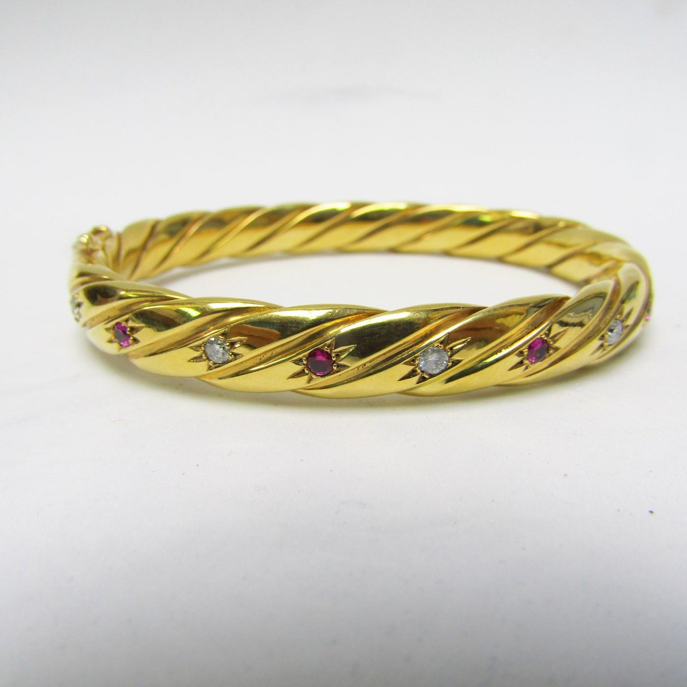 Pulsera Rígida y Oval, sogueada, en Oro de 18k con 5 Diamantes y 4 Rubíes, talla Brillante, de 0,50 ct. y 0,40 ct. respectivamente. Peso: 28 gr.